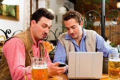Deux amis dans le pub bavarois avec l'ordinateur portatif Images stock