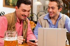 Deux amis dans le pub bavarois avec l'ordinateur portatif Images libres de droits
