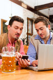 Deux amis dans le pub bavarois avec l'ordinateur portatif Photo libre de droits
