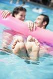 Deux amis dans une piscine se tenant sur un radeau gonflable avec des pieds collant hors de l'eau Image libre de droits