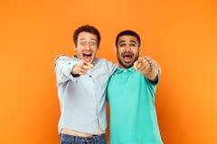Deux amis de bonheur s'étreignant, dirigeant le doigt et le l Photographie stock