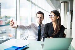 Deux amis de collègues portant à la photo leur l'individu s'asseyant dans le bureau, l'homme et la femme prenant le selfie avec l Image stock
