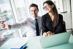 Deux amis de collègues portant à la photo leur l'individu s'asseyant dans le bureau, l'homme et la femme prenant le selfie avec l Photos stock