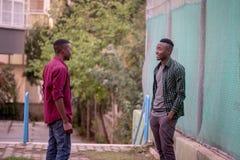 Deux amis de course noire conversant dans la rue Concept d'amis Image stock