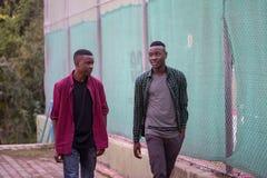 Deux amis de course noire marchant dans la rue Concept d'amis Image libre de droits