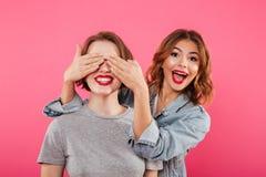 Deux amis de dames couvrant des yeux de mains Images stock