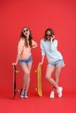 Deux amis de dames heureux tenant des planches à roulettes Image libre de droits