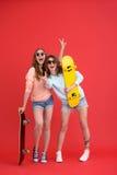 Deux amis de dames heureux tenant des planches à roulettes Photo stock