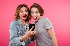 Deux amis de dames de sourire à l'aide du téléphone portable Image libre de droits