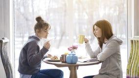Deux amis de femelle adulte mangeant et buvant du thé dans un café Photos libres de droits