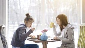 Deux amis de femelle adulte mangeant et buvant du thé dans un café Image libre de droits