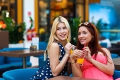 Deux amis de femme buvant du jus dans la barre Photographie stock libre de droits