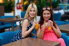 Deux amis de femme buvant du jus dans la barre Photo stock