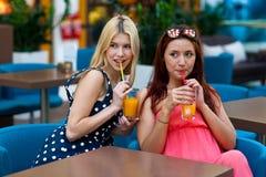 Deux amis de femme buvant du jus dans la barre Images stock