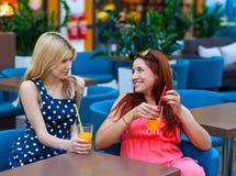 Deux amis de femme buvant du jus dans la barre Image libre de droits