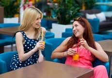 Deux amis de femme buvant du jus dans la barre Image stock