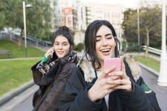 Deux amis de femme de joie de hippie à l'aide du téléphone intelligent Photographie stock libre de droits