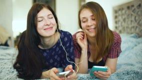Deux amis de femme de yuong écoutant la musique avec des écouteurs reliés au mensonge de smarhphone sur le lit banque de vidéos