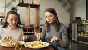Deux amis de femme mangent ensemble en café et parlent, appréciant leur nourriture banque de vidéos