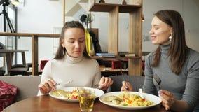 Deux amis de femme mangent ensemble en caf? et parlent, appr?ciant leur nourriture clips vidéos