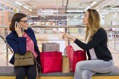 Deux amis de femme s'asseyant dans le mail après l'achat, regardant des sacs, se reposant Photos stock