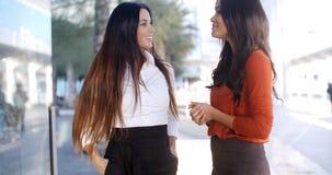 Deux amis de femmes élégantes se tenant causants Photographie stock