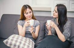 Deux amis de femmes ayant la conversation et buvant du café Photographie stock