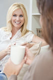 Deux amis de femmes buvant du thé ou du café à la maison Photo libre de droits