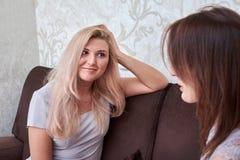 Deux amis de femmes causant sur le divan à la maison Image libre de droits