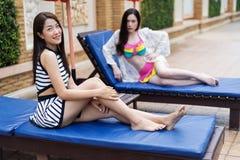 Deux amis de femmes détendant sur une chaise à la piscine Photos libres de droits