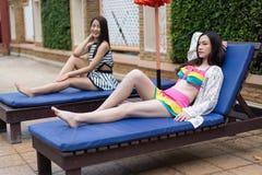 Deux amis de femmes détendant sur une chaise à la piscine Photo stock