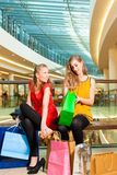 Deux amis de femmes faisant des emplettes dans un mail Photo stock