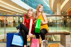 Deux amis de femmes faisant des emplettes dans un mail Photographie stock libre de droits