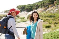 Deux amis de femmes marchant à la plage avec le sac et les vêtements Image libre de droits