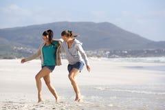 Deux amis de femmes marchant ensemble sur la plage Photos stock