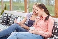 Deux amis de femmes parlant tenant des tasses de café Photos stock