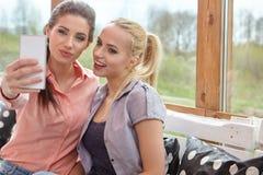 Deux amis de femmes parlant tenant des tasses de café Photo stock