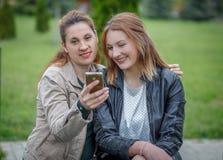 Deux amis de femmes partageant le media social dans le téléphone intelligent dehors Image libre de droits