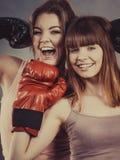 Deux amis de femmes portant des gants de boxe Images stock