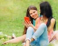 Deux amis de femmes riant et partageant des photos dans un téléphone intelligent Images libres de droits