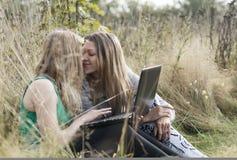Deux amis de femmes s'asseyant dehors ensemble Images libres de droits