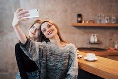 Deux amis de femmes s'asseyant en café et font le selfie Images stock