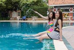 Deux amis de jeune femme éclaboussant l'eau dans la piscine Photographie stock libre de droits