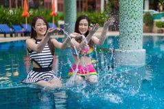 Deux amis de jeune femme éclaboussant l'eau dans la piscine Photos stock
