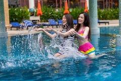 Deux amis de jeune femme éclaboussant l'eau dans la piscine Photos libres de droits