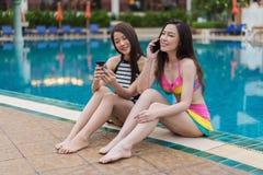 Deux amis de jeunes femmes à l'aide du téléphone portable dans la piscine Photos libres de droits