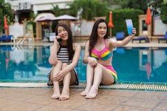 Deux amis de jeunes femmes à l'aide du téléphone portable dans la piscine Photo libre de droits