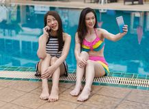 Deux amis de jeunes femmes à l'aide du téléphone portable dans la piscine Photographie stock libre de droits