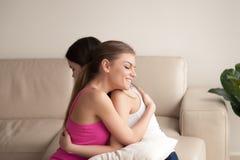Deux amis de jeunes femmes étreignant sur le sofa Photo libre de droits