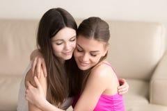 Deux amis de jeunes femmes embrassant doucement sur le sofa Photo stock